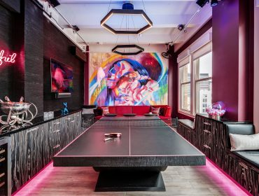 11 Ravens' Theseus Ping Pong table anchors a game room with a bold fuchsia color palette and striking art.